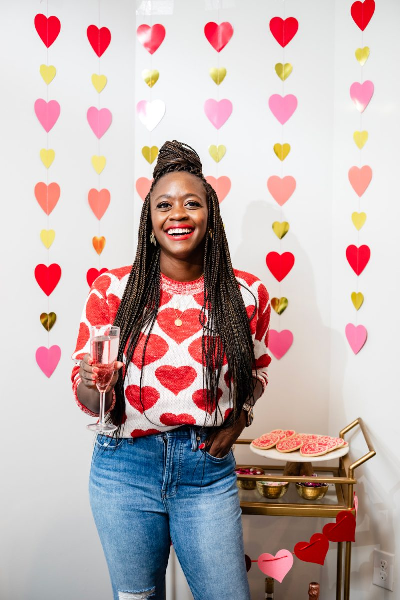 How to Style a Galentine's Day Bar Cart by popular DC lifestyle blogger, Alicia Tenise: image of a woman wearing a Lou & Grey Heart You Sweater and standing next to a Target Threshold Wood & Brass Finish Bar Cart with fresh pink roses, heart shaped sugar cookies, Amazon ZOOYOO pink/gold Paper Straw, heart napkins, heart garland, and alcoholic beverages on it that's in front of a Target Spritz 6ct DIY Valentine's Paper Heart Streamer backdrop.