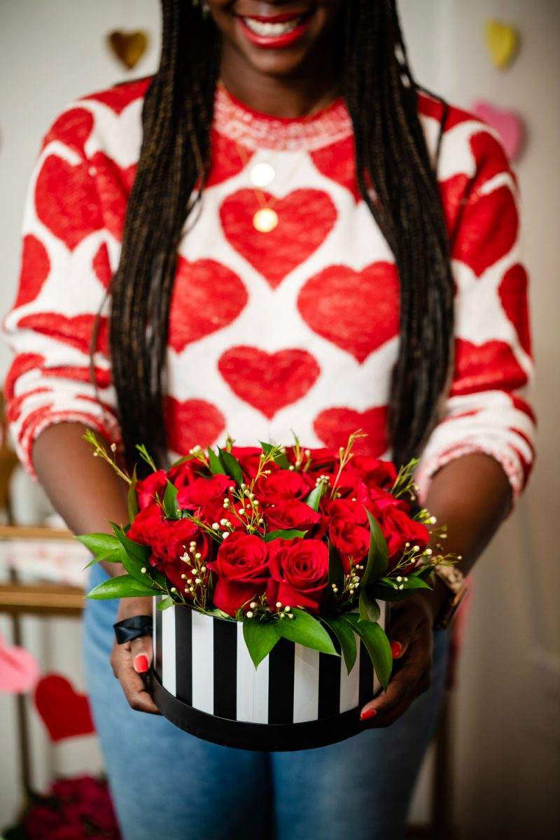 How to Help Others During COVID-19 by popular lifestyle blogger, Alicia Tenise: image of a woman wearing a heart sweater and holding a black and white striped hat box filled with red roses.