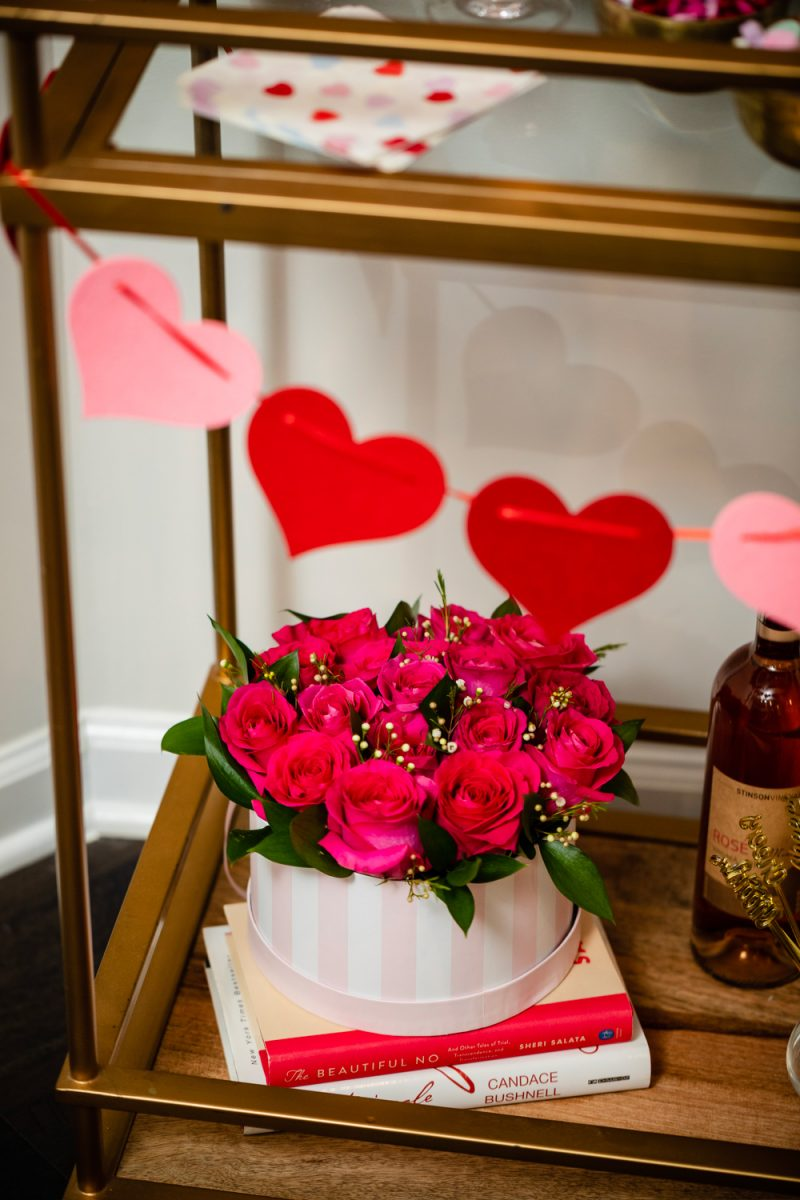 How to Style a Galentine's Day Bar Cart by popular DC lifestyle blogger, Alicia Tenise: image of a Target Threshold Wood & Brass Finish Bar Cart with fresh pink roses, heart shaped sugar cookies, Amazon ZOOYOO pink/gold Paper Straw, heart napkins, glasses, valentine's candy in gold bowls, heart garland, and alcoholic beverages on it that's in front of a Target Spritz 6ct DIY Valentine's Paper Heart Streamer backdrop.