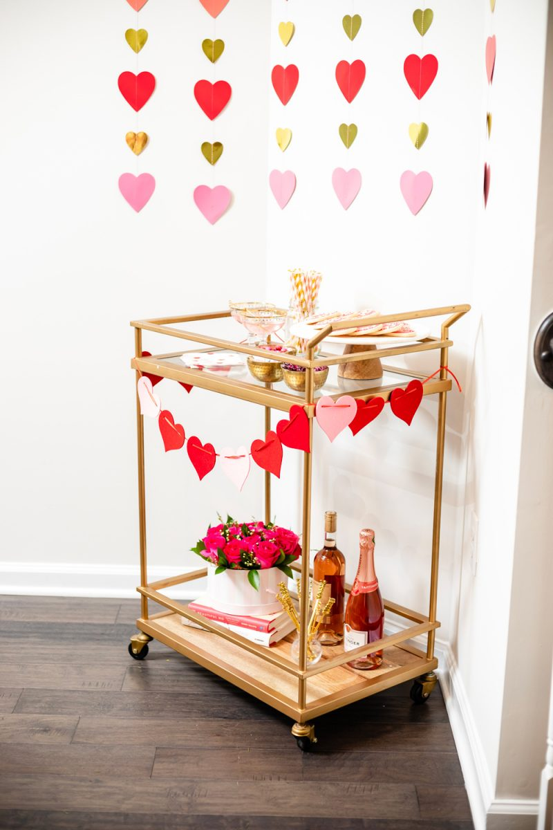 How to Style a Galentine's Day Bar Cart by popular DC lifestyle blogger, Alicia Tenise: image of a Target Threshold Wood & Brass Finish Bar Cart with fresh pink roses, heart shaped sugar cookies, Amazon ZOOYOO pink/gold Paper Straw, heart napkins, heart garland, and alcoholic beverages on it that's in front of a Target Spritz 6ct DIY Valentine's Paper Heart Streamer backdrop.