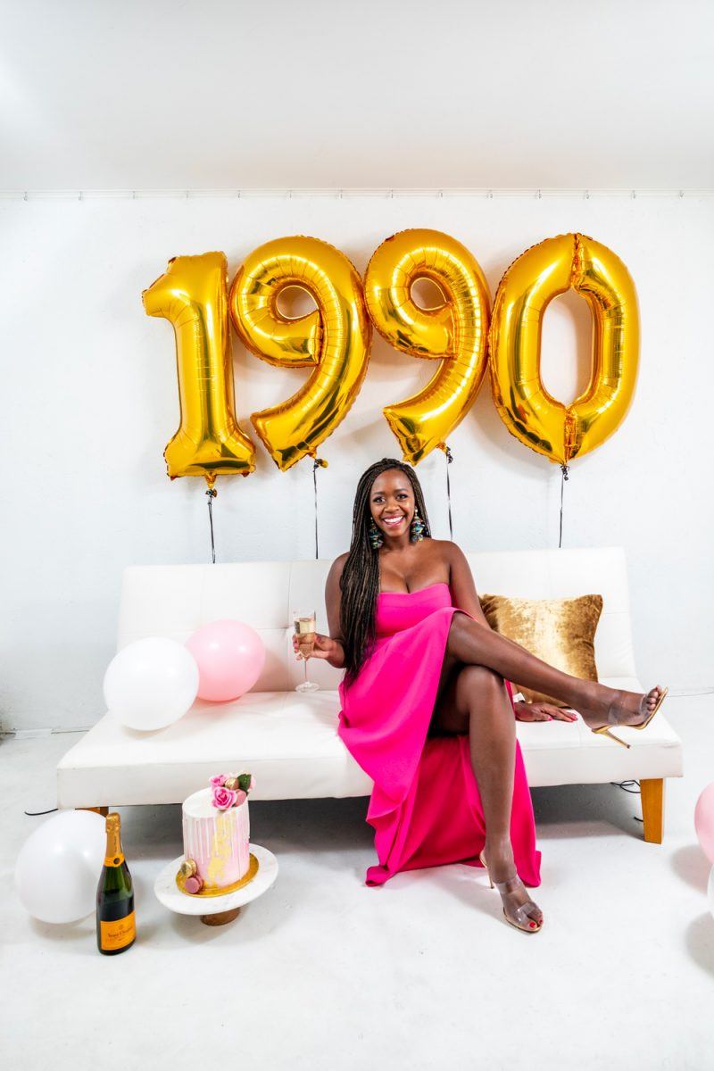 30 Birthday Party Decorations | Turning 30 by popular lifestyle blogger, Alicia Tenise: image of a woman wearing a Rent the Runway LIKELY  ADD TO HEARTS High Low Lovelle Gown and sitting on a white couch next to a Maliha Creations cake on a Target Marble & Acacia Cake Stand and some Amazon 40 Inch Gold Digital Helium Foil Birthday Party Balloons.