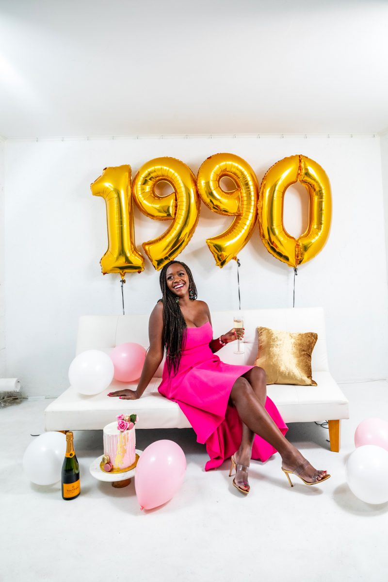 30th Birthday Inspiration | Turning 30 by popular lifestyle blogger, Alicia Tenise: image of a woman wearing a Rent the Runway LIKELY  ADD TO HEARTS High Low Lovelle Gown and sitting on a white couch next to a Maliha Creations cake on a Target Marble & Acacia Cake Stand and some Amazon 40 Inch Gold Digital Helium Foil Birthday Party Balloons.