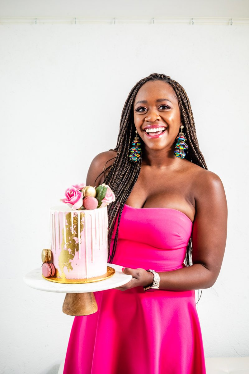 Best Birthday Cake Charlottesville | Turning 30 by popular lifestyle blogger, Alicia Tenise: image of a woman wearing a Rent the Runway LIKELY  ADD TO HEARTS High Low Lovelle Gown and holding a Maliha Creations cake on a Target Marble & Acacia Cake Stand.