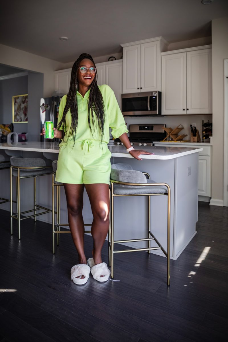 Best Loungewear for Spring | Best Loungewear by popular DC fashion blogger, Alicia Tenise: image of a woman standing in her kitchen and wearing a Lou & Grey Signaturesoft Plush Zip Top, Lou & Grey Signaturesoft Plush Drawstring Shorts, fuzzy sandal slippers, and Warby Parker Durand glasses.