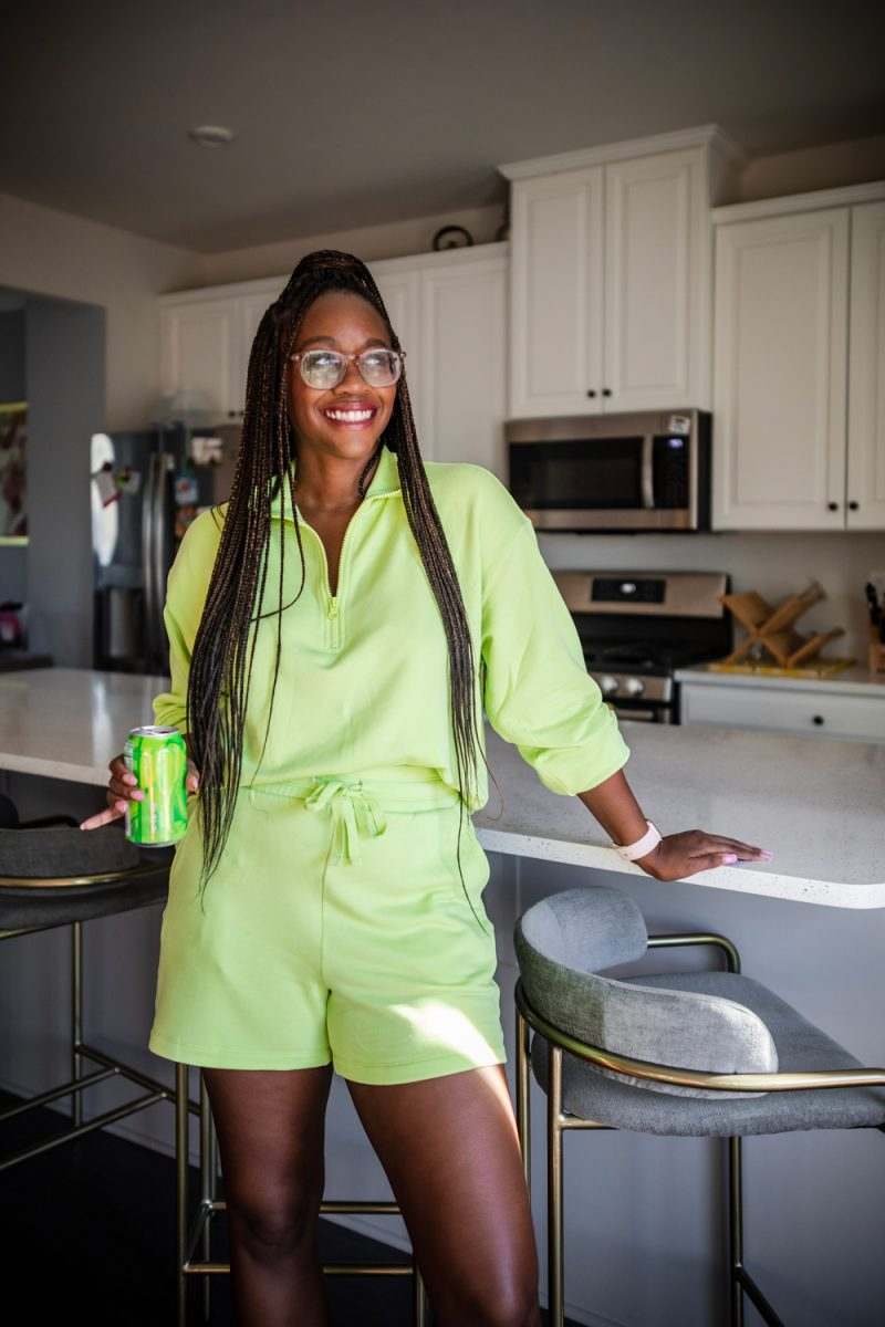 Lime Green Loungewear for Spring | Best Loungewear by popular DC fashion blogger, Alicia Tenise: image of a woman standing in her kitchen and wearing a Lou & Grey Signaturesoft Plush Zip Top, Lou & Grey Signaturesoft Plush Drawstring Shorts, fuzzy sandal slippers, and Warby Parker Durand glasses.