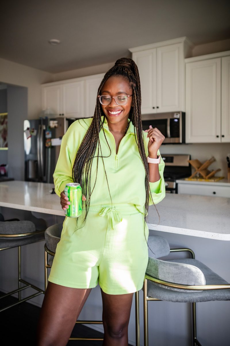 What to Wear While Working from Home | Best Loungewear by popular DC fashion blogger, Alicia Tenise: image of a woman standing in her kitchen and wearing a Lou & Grey Signaturesoft Plush Zip Top, Lou & Grey Signaturesoft Plush Drawstring Shorts, fuzzy sandal slippers, and Warby Parker Durand glasses.