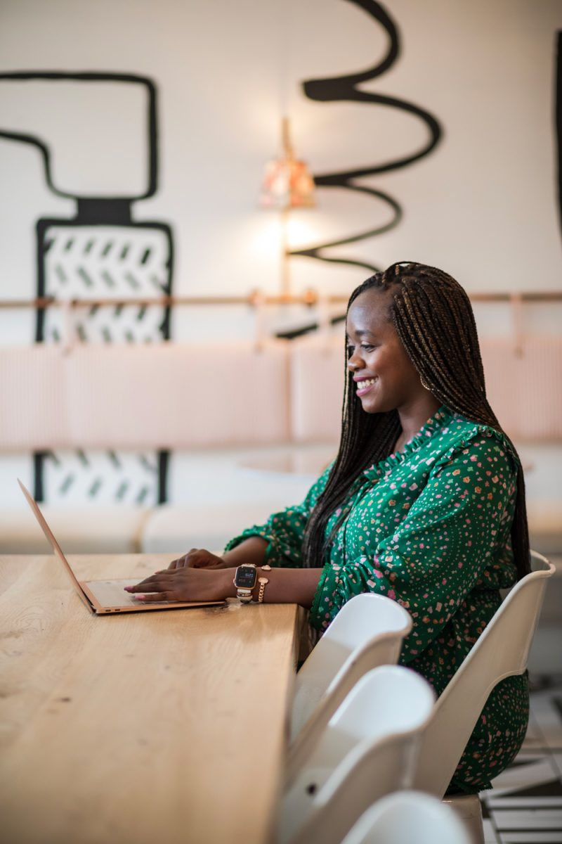 H&R Block Tax Pro Go review: self employed tax tips featured by top DC lifestyle blogger and influencer, Alicia Tenise | Self Employed Tax Tips by popular DC lifestyle blogger, Alicia Tenise: image of a woman wearing a green floral maxi dress and sitting at a table while she works on her laptop.