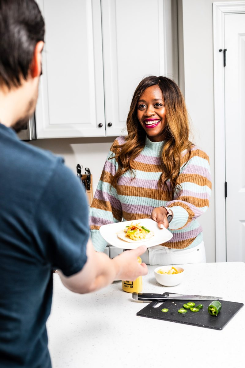 Stay At Home Date Ideas by popular DC lifestyle blogger, Alicia Tenise: image of a woman handing a man a plate of food.