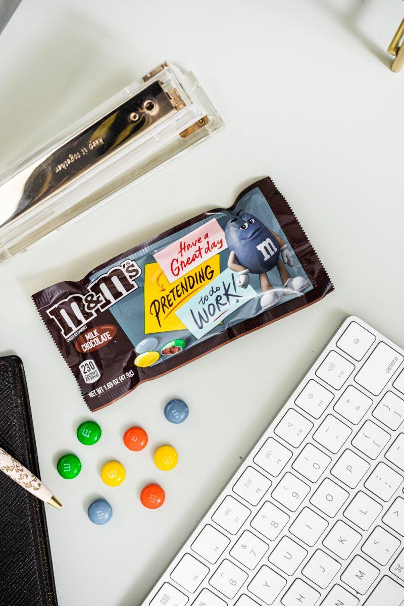 Realistic Work From Home Tips by popular DC lifestyle blogger, Alicia Tenise: image of a wireless keyboard, a bag of M&M's and a acrylic stapler.