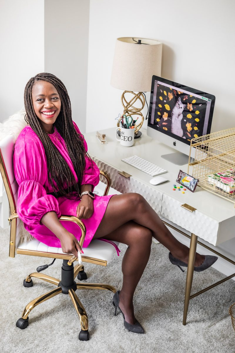Realistic Work From Home Tips by popular DC lifestyle blogger, Alicia Tenise: image of a woman wearing a pink dress, black tights, and black pumps and sitting in a Bed Bath and Beyond LumiSource Master Adjustable Office Chair at a West Elm Audrey Desk.