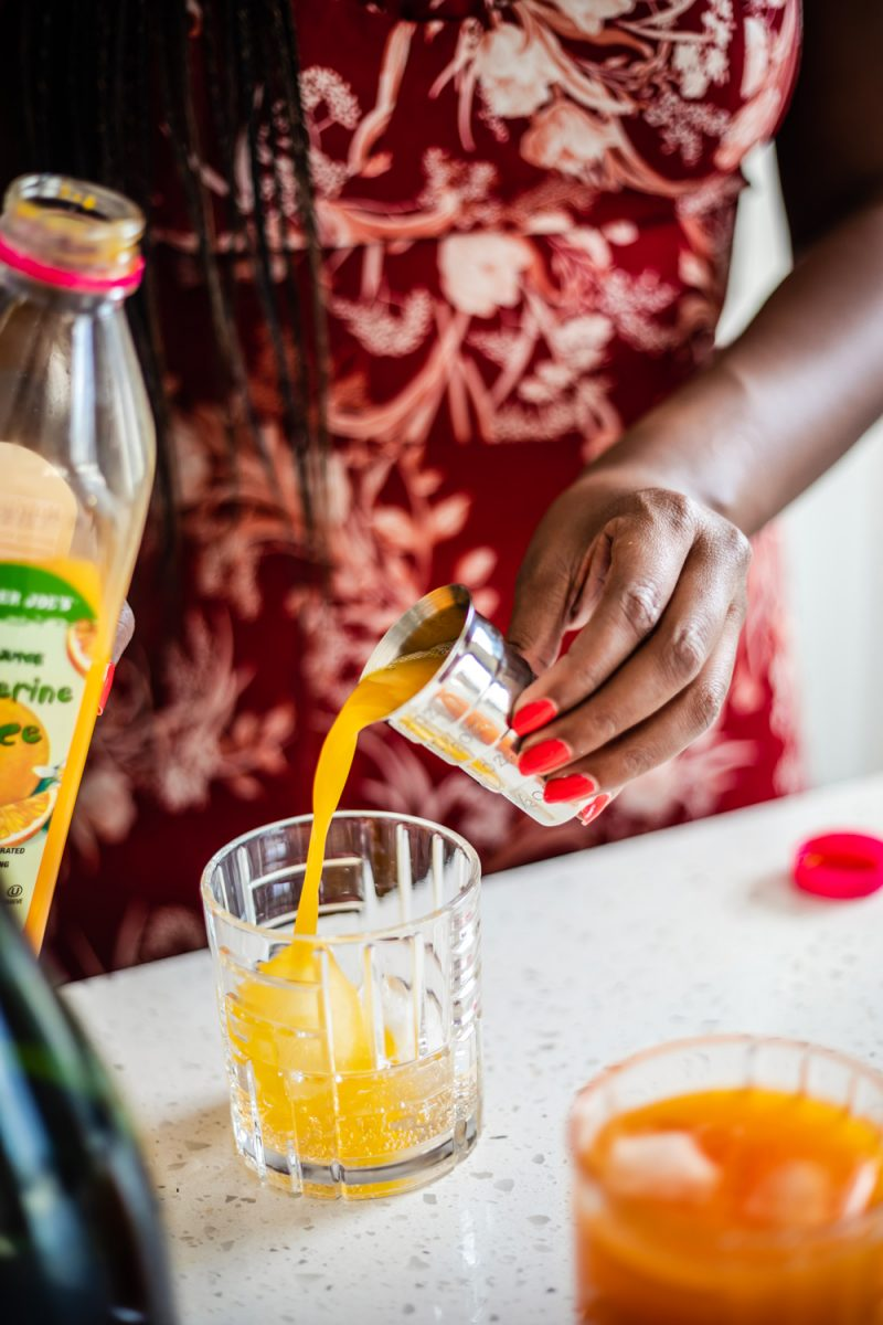 Trader Joe's Tangerine Juice | Aperol Tangerine Mimosa by popular D.C. lifestyle blogger, Alicia Tenise: image of a woman making a Aperol Tangerine Mimosa.