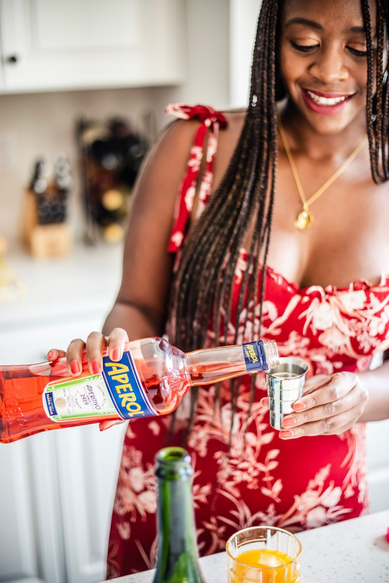 Aperol Cocktail | Aperol Tangerine Mimosa by popular D.C. lifestyle blogger, Alicia Tenise: image of a woman making a Aperol Tangerine Mimosa.