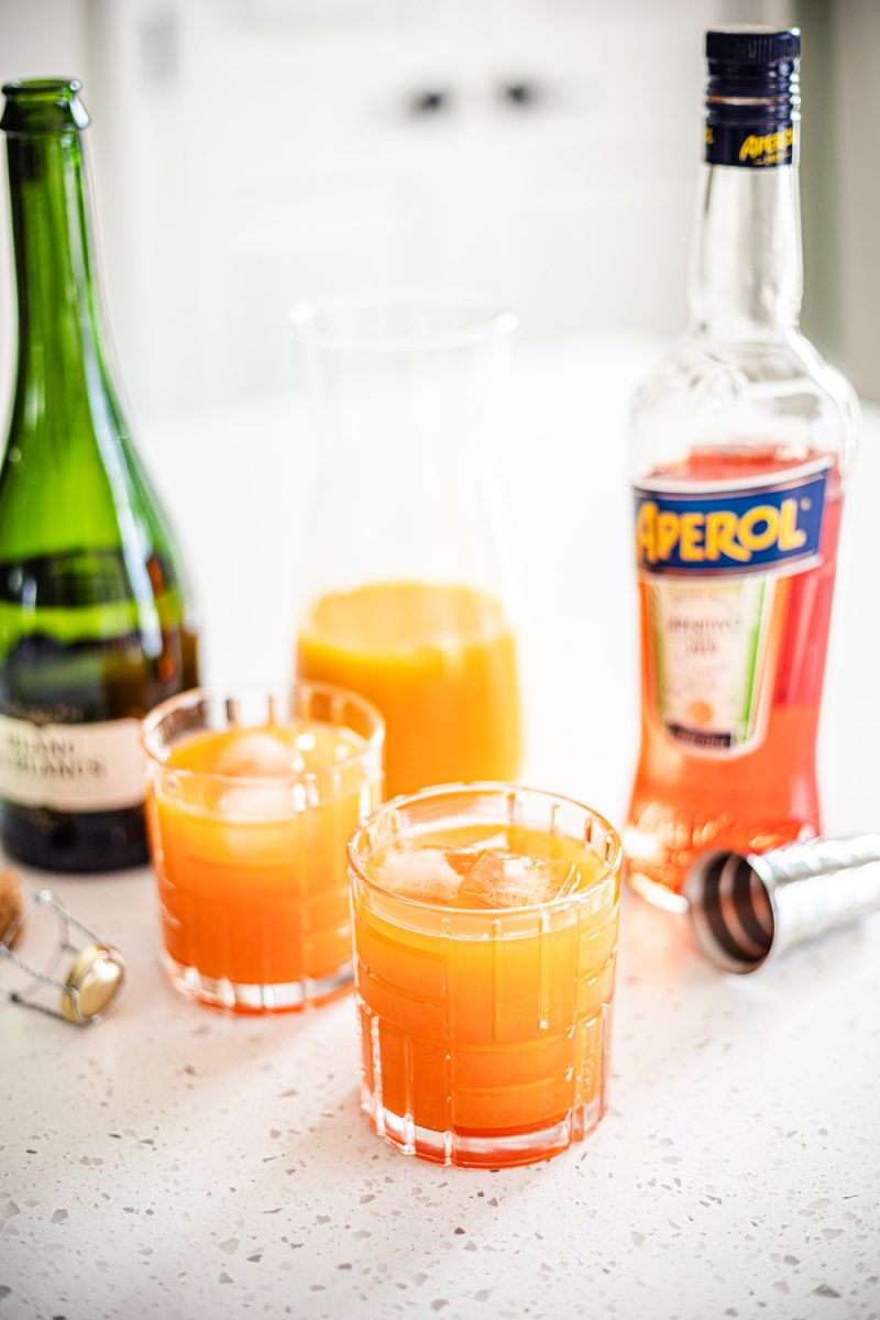 Aperol Tangerine Mimosa Recipe - Aperol Cocktails | Aperol Tangerine Mimosa by popular D.C. lifestyle blogger, Alicia Tenise: image of a white wine bottle, Aperol spritz, orange juice in a glass flask, and glasses filled with Tangerine mimosas.