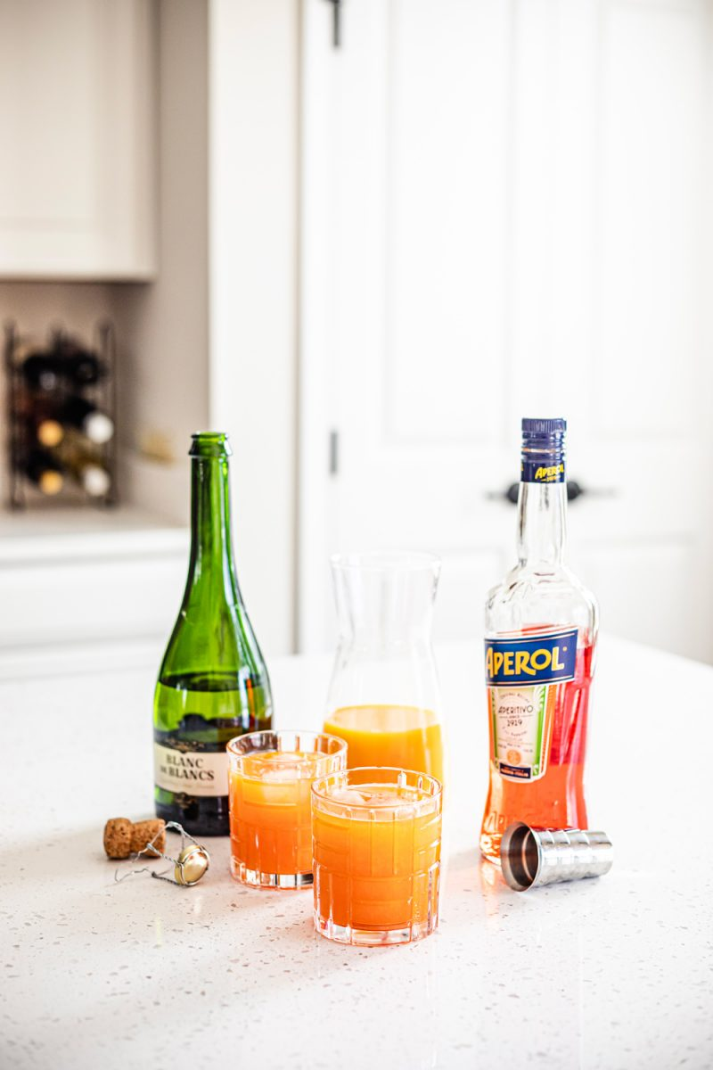 Aperol Tangerine Mimosa | Aperol Tangerine Mimosa by popular D.C. lifestyle blogger, Alicia Tenise: image of a white wine bottle, Aperol spritz, orange juice in a glass flask, and glasses filled with Tangerine mimosas.