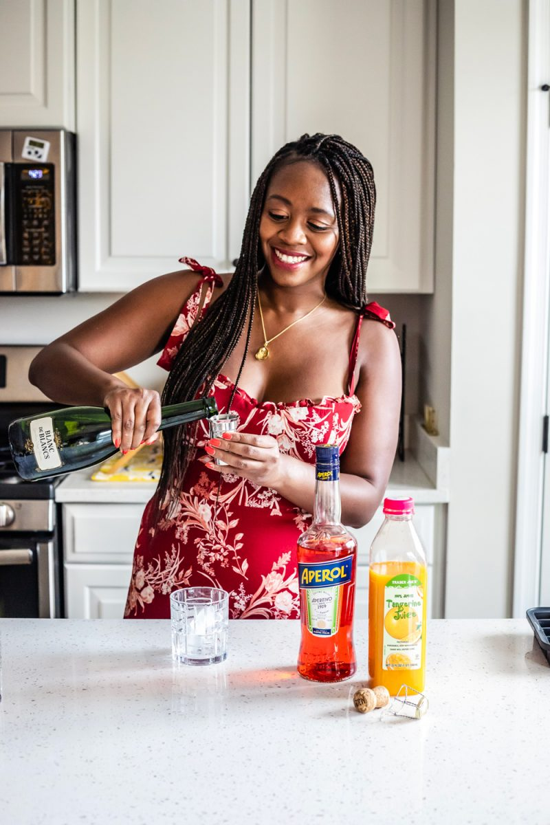 Aperol Tangerine Mimosa by popular D.C. lifestyle blogger, Alicia Tenise: image of a woman making a Aperol Tangerine Mimosa.