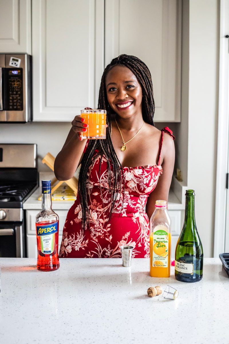 Reformation Nikita Dress in Juliette, Aperol Cocktail Idea | Aperol Tangerine Mimosa by popular D.C. lifestyle blogger, Alicia Tenise: image of a woman making a Aperol Tangerine Mimosa.