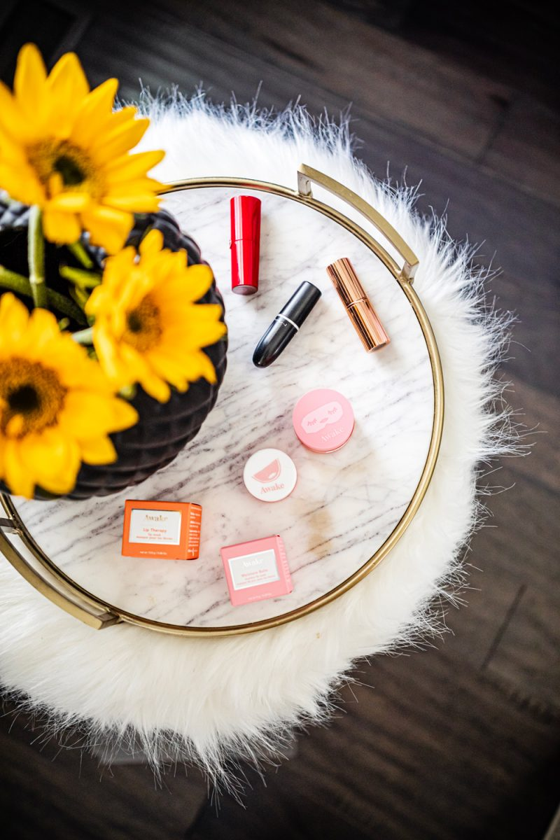 Awake Beauty Lip Therapy review featured by top DC life and style blog, Alicia Tenise | Awake Beauty Lip Therapy by popular D.C. beauty blogger, Alicia Tenise: image of Awake Beauty Lip Therapy products and three lipstick tubes on a marble tray with gold handles.