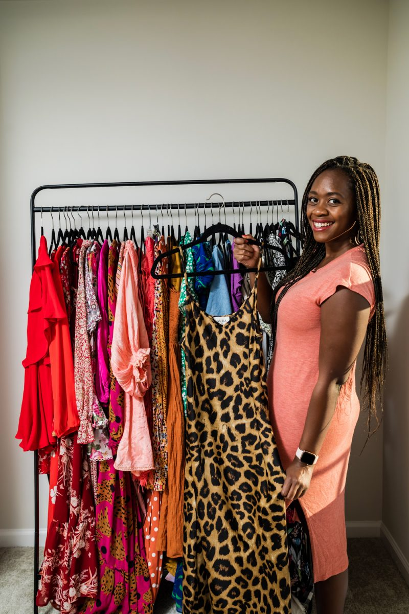 How to Purge Your Closet by popular D.C. lifestyle blogger, Alicia Tenise: image of a woman standing next to a clothing rack filled with colorful clothes.