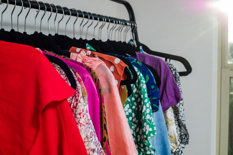 How to Purge Your Closet by popular D.C. lifestyle blogger, Alicia Tenise: image of a clothing rack filled with colorful clothes.