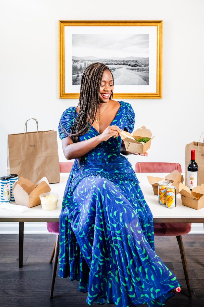 Charlottesville Small Businesses to Support, Common House Takeout Food Options, Self Portrait Printed Crescent Dress | Charlottesville Small Businesses by popular D.C. lifestyle blogger, Alicia Tenise: image of a woman wearing a blue and green print maxi dress and sitting on her table full of takeout food and holding a carryout box.