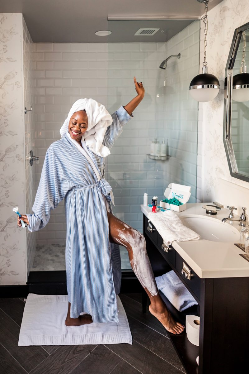 Self Care Ideas by popular DC lifestyle blogger, Alicia Tenise: image of a woman shaving her legs in her bathroom and wearing a blue and white striped bathrobe and a white towel wrap on her head.