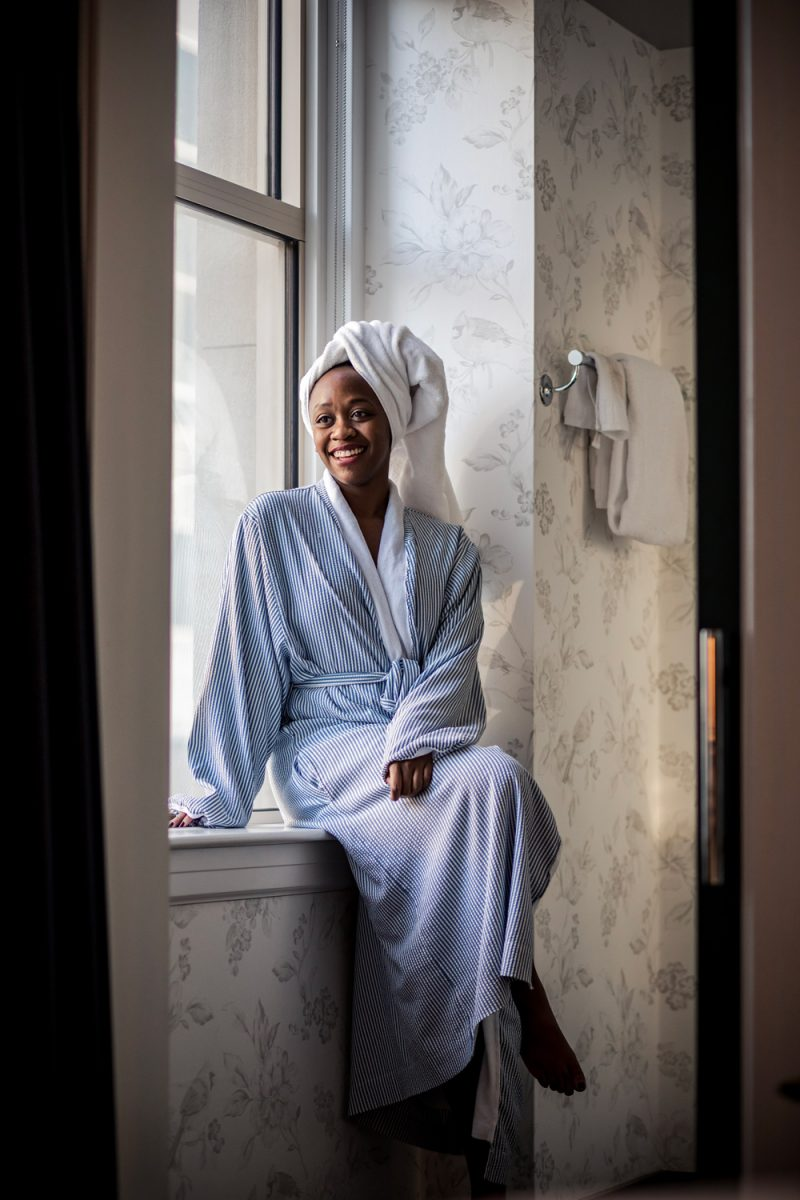 Self Care Ideas by popular DC lifestyle blogger, Alicia Tenise: image of a woman sitting on her bathroom window ledge and wearing a blue and white striped bathrobe and a white towel wrap on her head.