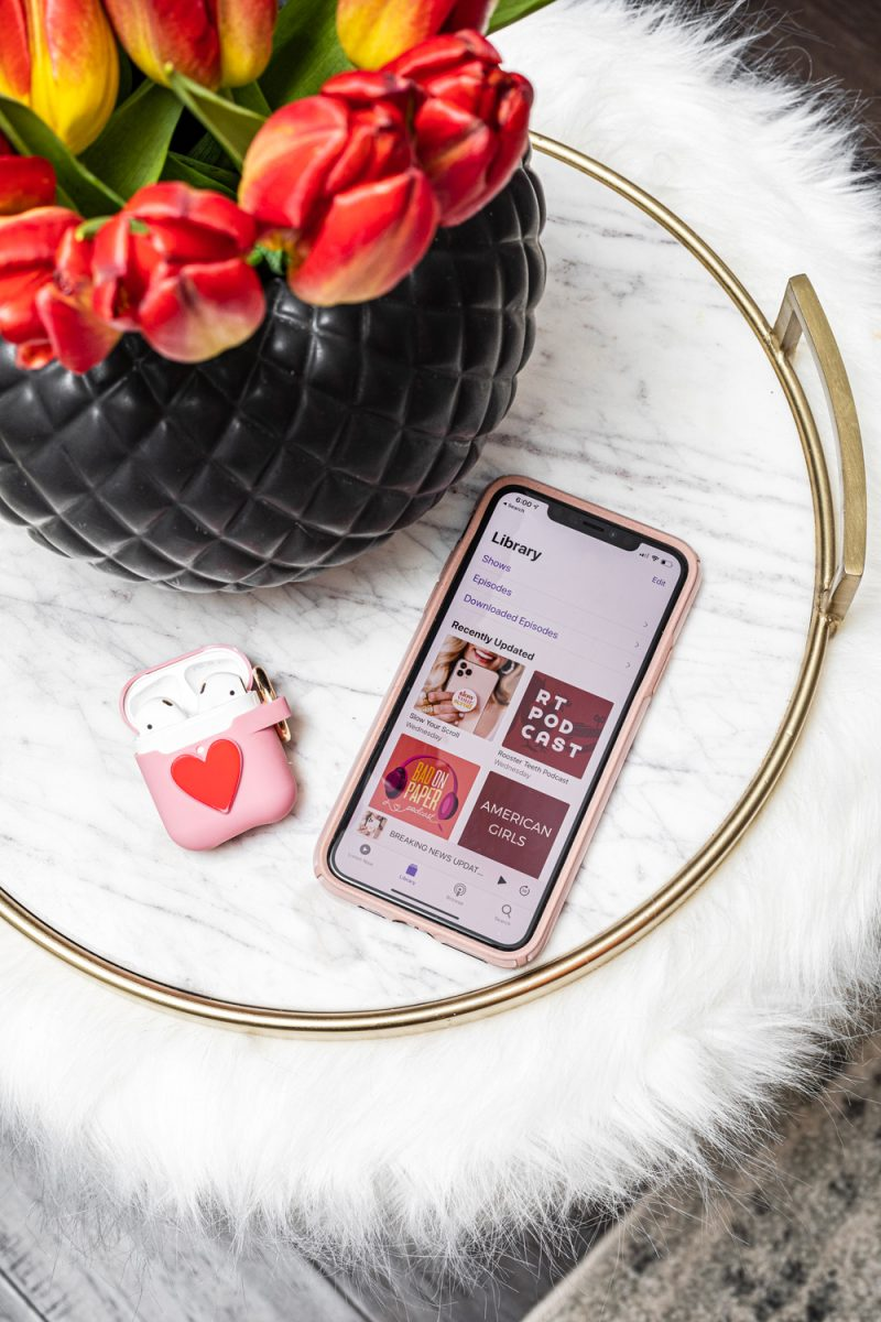 The best podcasts for women | Most Addictive Podcasts by popular D.C. lifestyle blogger, Alicia Tenise: image of a smartphone and airpods case next to a black vase filled with red tulips.