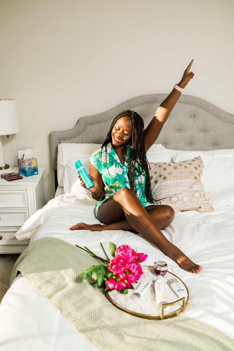 Sunscreens for Dark Skin by popular beauty blogger, Alicia Tenise: image of a woman sitting on her bed and wearing palm frond print pajamas while holding a bottle of sunscreen and sitting next to a marble serving tray will pink roses and other various sunscreen products on it.