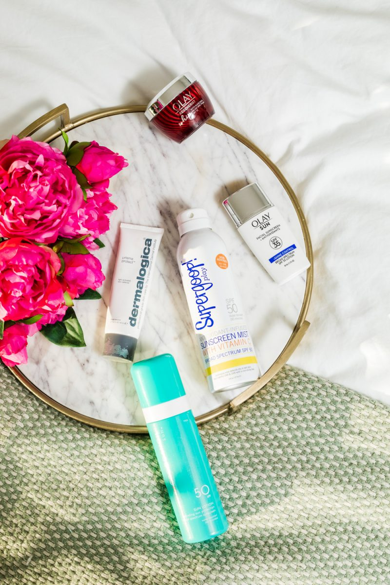 The Best Sunscreens for Dark Skin   Sunscreens for Dark Skin by popular beauty blogger, Alicia Tenise: image of a marble serving tray will pink roses, Olay whips sunscreen, Olay Sun facial sunscreen, Dermalogica sunscreen, Supergoop Play sunscreen mist, and Moroccanoil sun lotion.