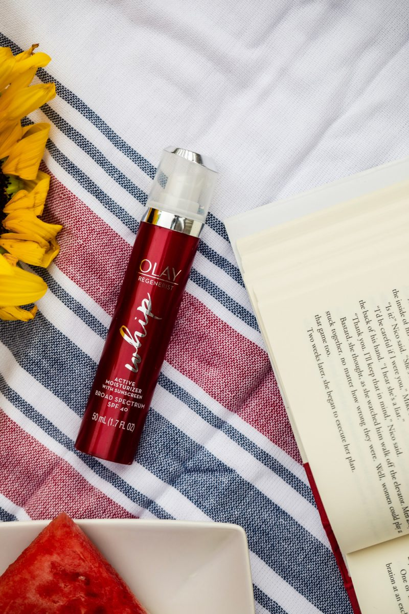 Olay Regenerist Whip review and summer self care routine featured by top D.C beauty blogger, Alicia Tenise | Self Care Routine by popular D.C. lifestyle blog, Alicia Tenise: image of a bottle of Olay Regenerist whip on a red, white, and blue stripe turkish towel next to a open book and a white plate with a watermelon slice on it.