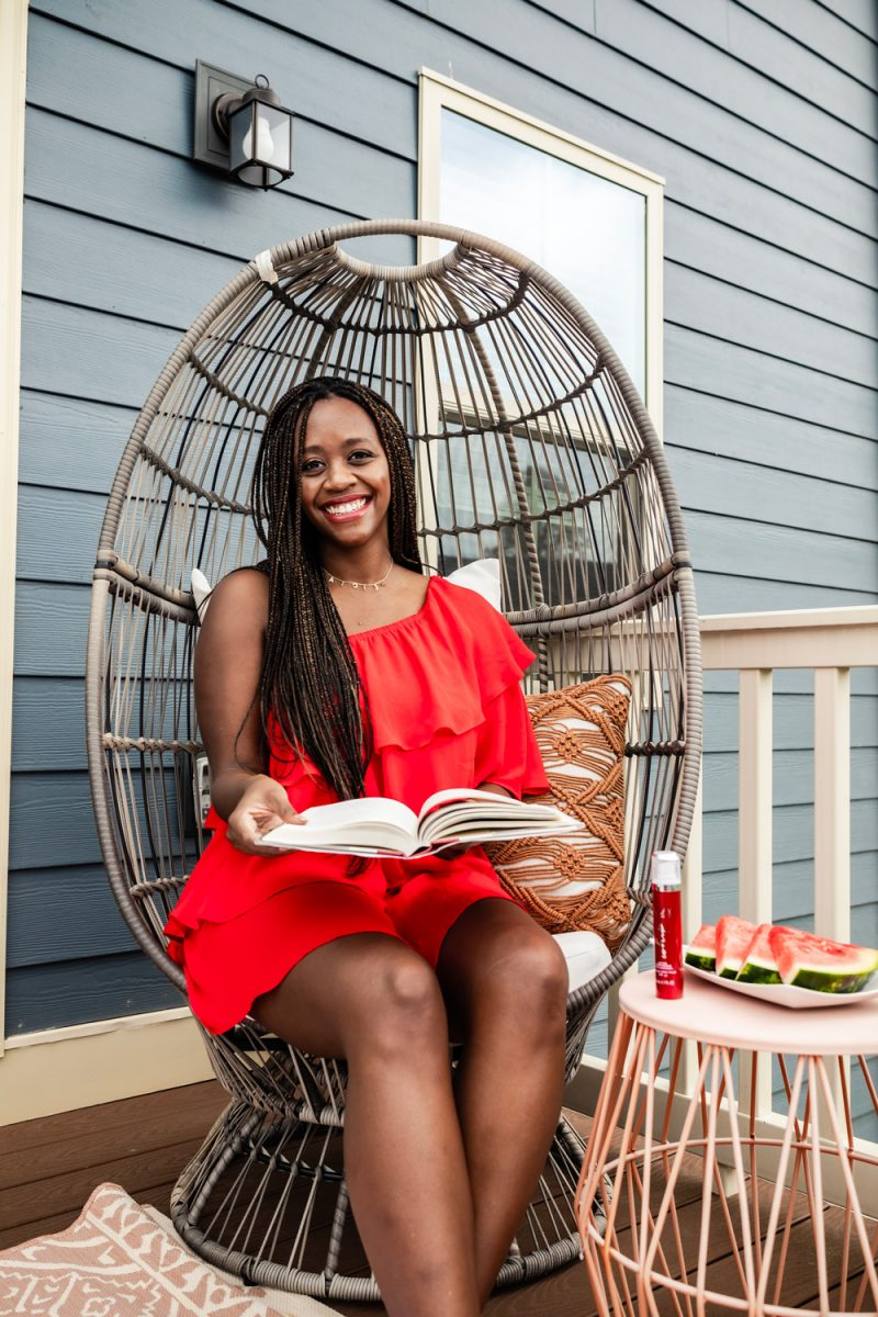 Olay Regenerist Whip review and summer self care routine featured by top D.C beauty blogger, Alicia Tenise | Self Care Routine by popular D.C. lifestyle blog, Alicia Tenise: image of Alicia Tenise wearing a red ruffle dress and sitting in a rattan chair next to a end table that has a plate of sliced watermelon and a bottle of Olay Rengenerist Whip on it.