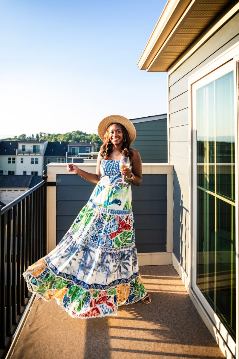 FARM RIO BLUE TILE MAXI DRESS | Wine School by popular D.C. lifestyle blog, Alicia Tenise: image of Alicia Tenise standing on her patio and wearing a Farm Rio blue tile Maxi Dress, ShopBop Hat Attack Day To Day Continental Hat, Dolce Vita Noles Heeled Slide, and Kendra Scott Fallyn Hoop Earrings In Rose Gold while holding a glass of wine.