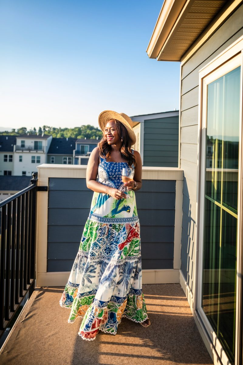 Wine School by popular D.C. lifestyle blog, Alicia Tenise: image of Alicia Tenise standing on her patio and wearing a Farm Rio blue tile Maxi Dress, ShopBop Hat Attack Day To Day Continental Hat, Dolce Vita Noles Heeled Slide, and Kendra Scott Fallyn Hoop Earrings In Rose Gold while holding a glass of wine.