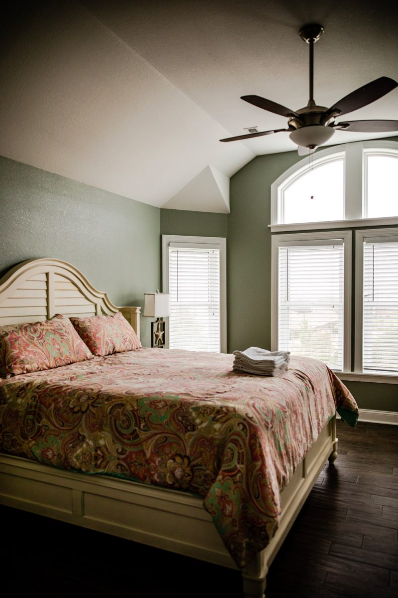 Resort Realty Outer Banks | Things to do in the Outer Banks by popular D.C. travel blogger, Alicia Tenise: image of a bedroom with a ceiling fan, star fish lamp, and king size bed.