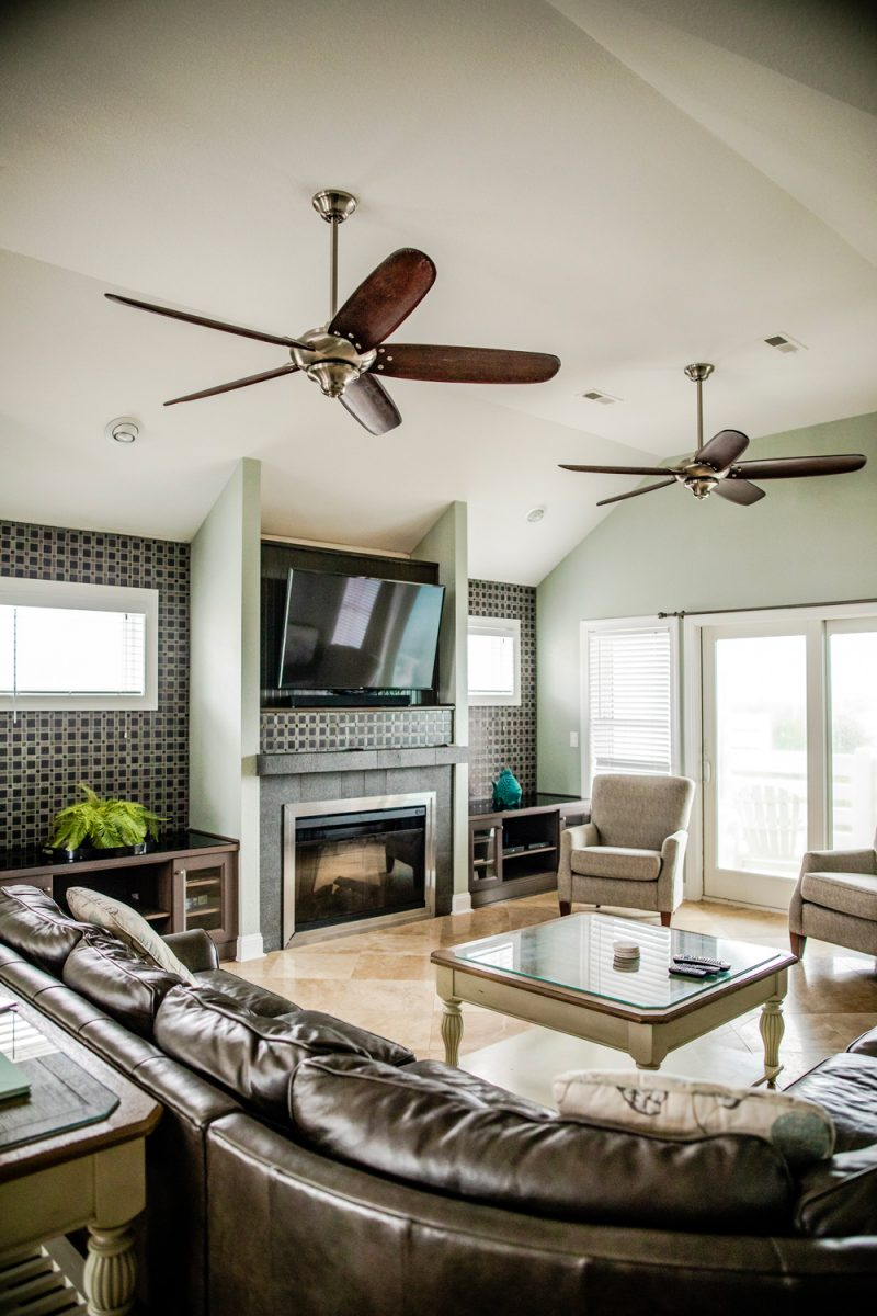 Resort Realty Outer Banks | Things to do in the Outer Banks by popular D.C. travel blogger, Alicia Tenise: image of a living room with a leather sectional couch, plasma T.V. glass coffee table, and ceiling fans.