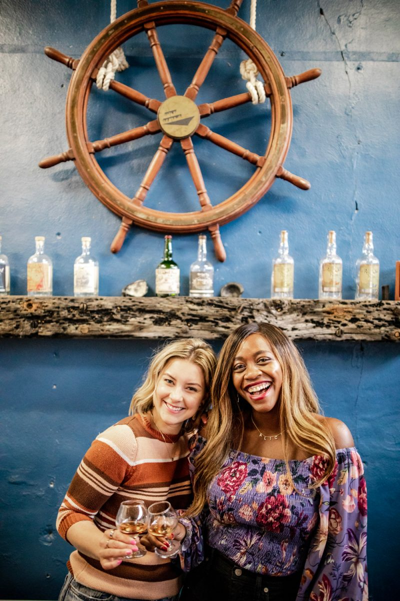 Kill Devil Rum (Outer Banks Distilling Company) | Things to do in the Outer Banks by popular D.C. travel blogger, Alicia Tenise: image of Alicia Tenise and her friend at Kill Devil Rum.
