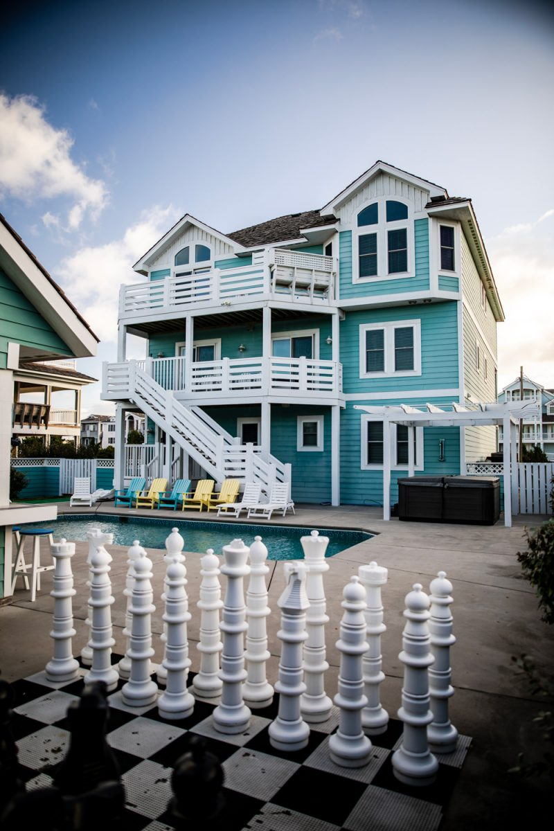 Resort Realty Outer Banks - Landfall II Things to do in the Outer Banks by popular D.C. travel blogger, Alicia Tenise: image of a blue house with a pool and a life size chess board.