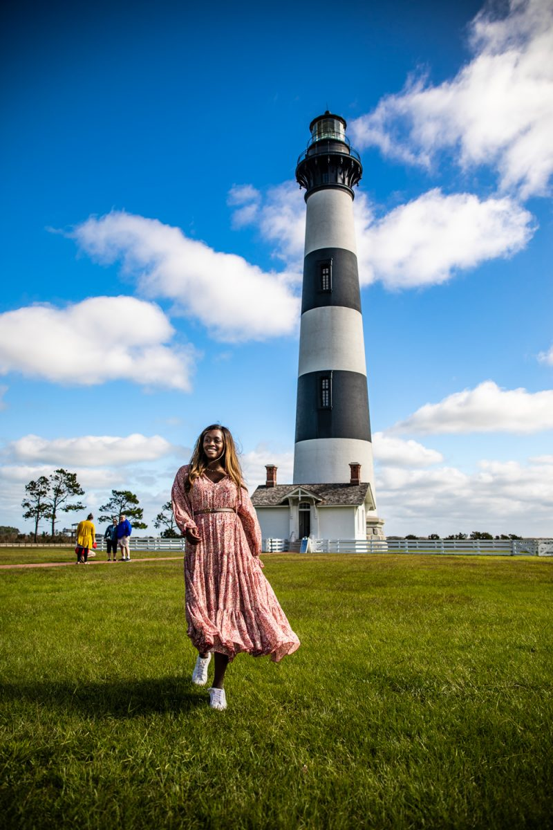 Bodie Island Lighthouse | Things to do in the Outer Banks by popular D.C. travel blogger, Alicia Tenise: image of Alicia Tenise standing in front of Bodie Island lighthouse.