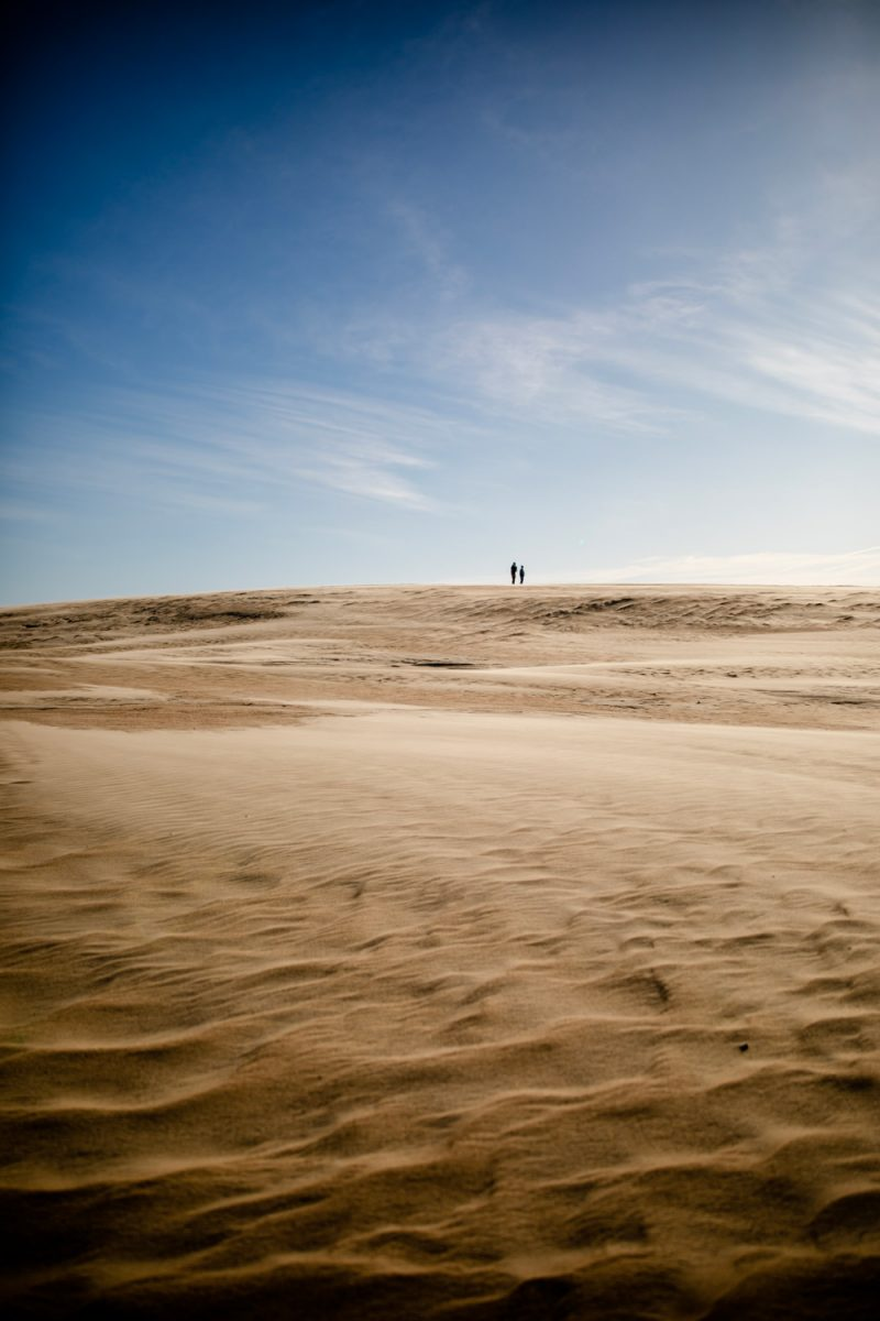 Jockey's Ridge State Park | Things to do in the Outer Banks by popular D.C. travel blogger, Alicia Tenise: image of a man and woman standing in the sand at Jockey's Ridge state park.