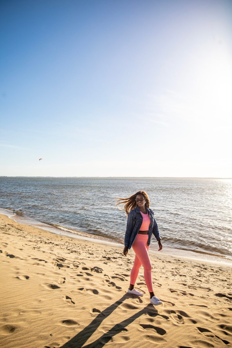 Jockey's Ridge State Park | Things to do in the Outer Banks by popular D.C. travel blogger, Alicia Tenise: image of Alicia Tenise walking in the sand at Jockey's Ridge state park.