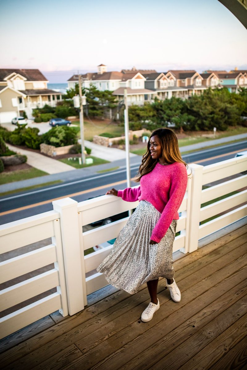 Where to Stay in the Outer Banks | Things to do in the Outer Banks by popular D.C. travel blogger, Alicia Tenise: image of Alicia Tenise standing on a deck and wearing a pink sweater and black and white animal print skirt.