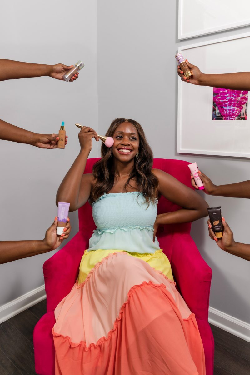 Best Tarte Foundations by popular D.C. beauty blogger, Alicia Tenise: image of Alicia Tenise wearing a multi color tiered maxi dress and sitting in a pink arm chair as she applies a makeup brush to her face and is surrounded by various Tarte foundations.