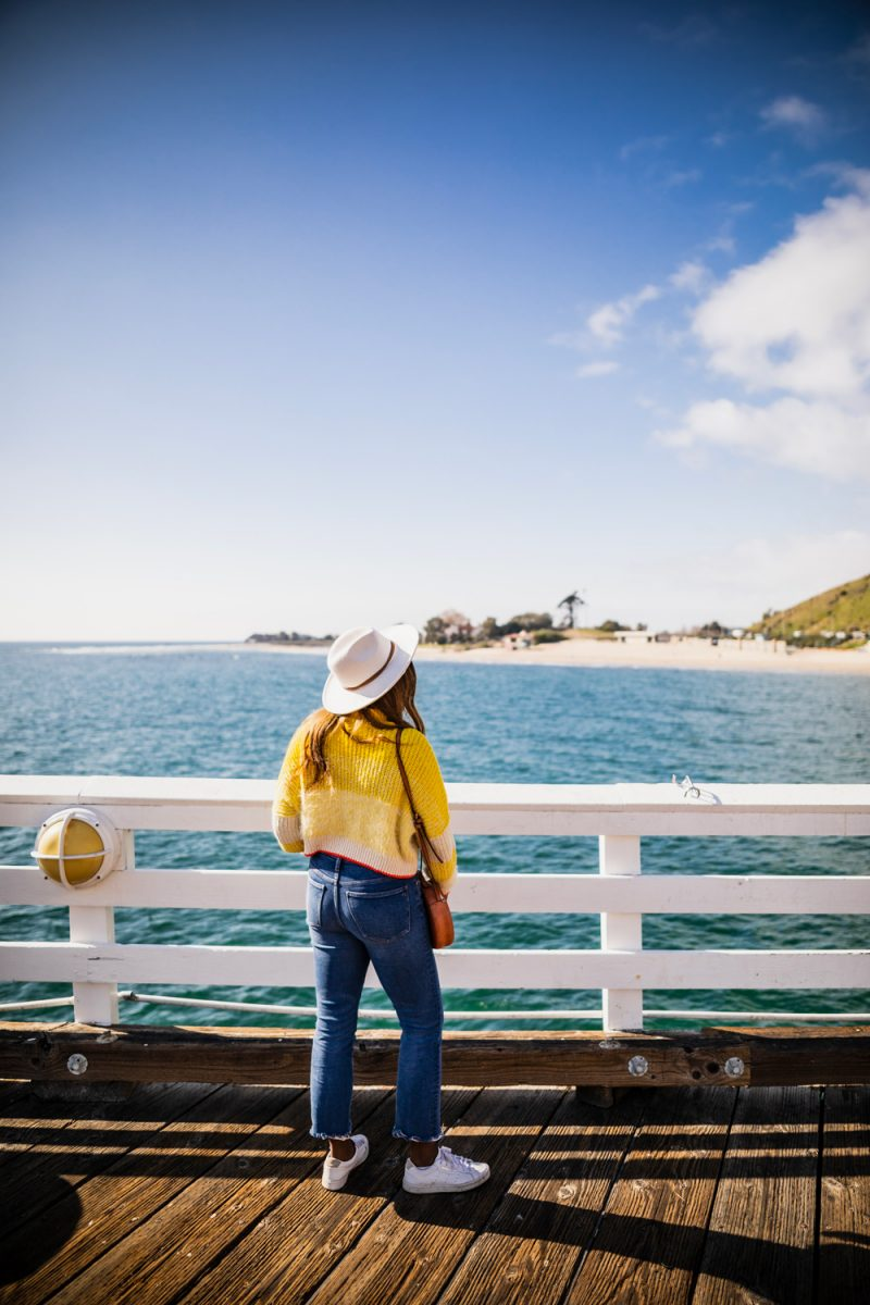 Malibu Pier | Taking Antidepressants by popular D.C. lifestyle blogger, Alicia Tenise: image of a woman wearing a yellow cable knit sweater, jeans, white sneakers, and a white fedora while standing on Malibu Pier.