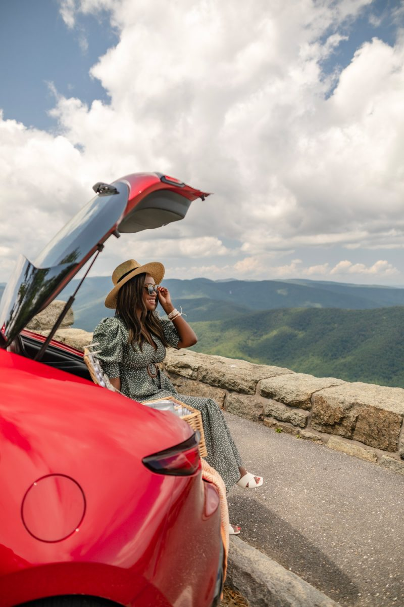 Socially Distanced Road Trip Ideas: The Best Weekend Getaways from DC | Road Trip Ideas by popular D.C. travel blogger, Alicia Tenise: image of Alicia Tenise sitting in the back of her red car and looking out over a view of mountains and valleys.