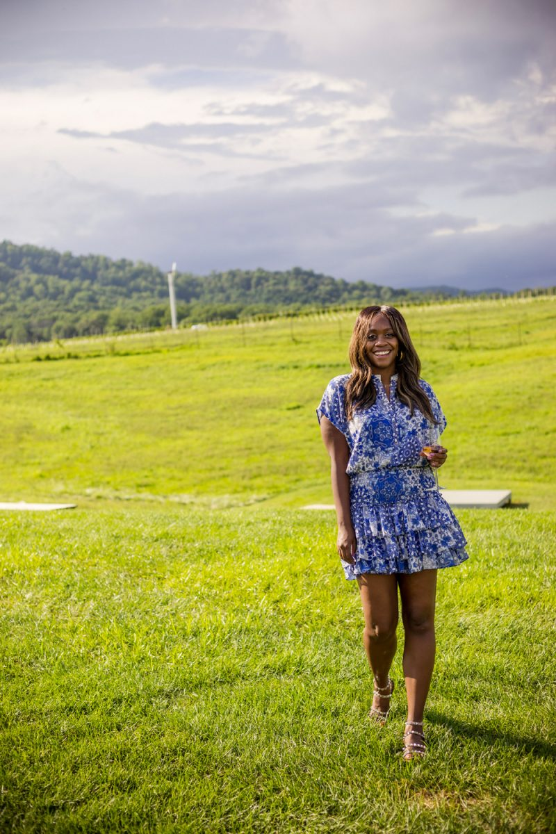 Early Mountain Vineyards | Wine 101 by popular D.C. lifestyle blogger, Alicia Tenise: image of Alicia Tenise standing outside at a winery and wearing a Eloisa Dress  MISA Los Angeles brand: MISA Los Angeles, Steve Madden Women's Travel Rock Stud Flat Sandals, GOLD DORADO MIYUKI BEADS APPLE WATCH STRAP, and The Sis Kiss It's All in a Name™ Personalized Necklace while holding a glass of wine.