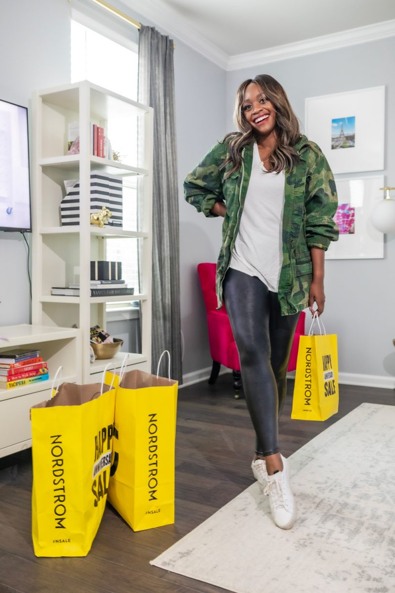Last minute Nordstrom Anniversary Sale picks by top VA fashion blogger, Alicia Tenise | Nordstrom Anniversary Sale by popular D.C. fashion blog, For the Love: image of Alicia Tenise standing next to some Nordstrom Anniversary Sale shopping bags in her living room and wearing a Nordstrom camo jacket and Nordstrom Spanx faux leather leggings.
