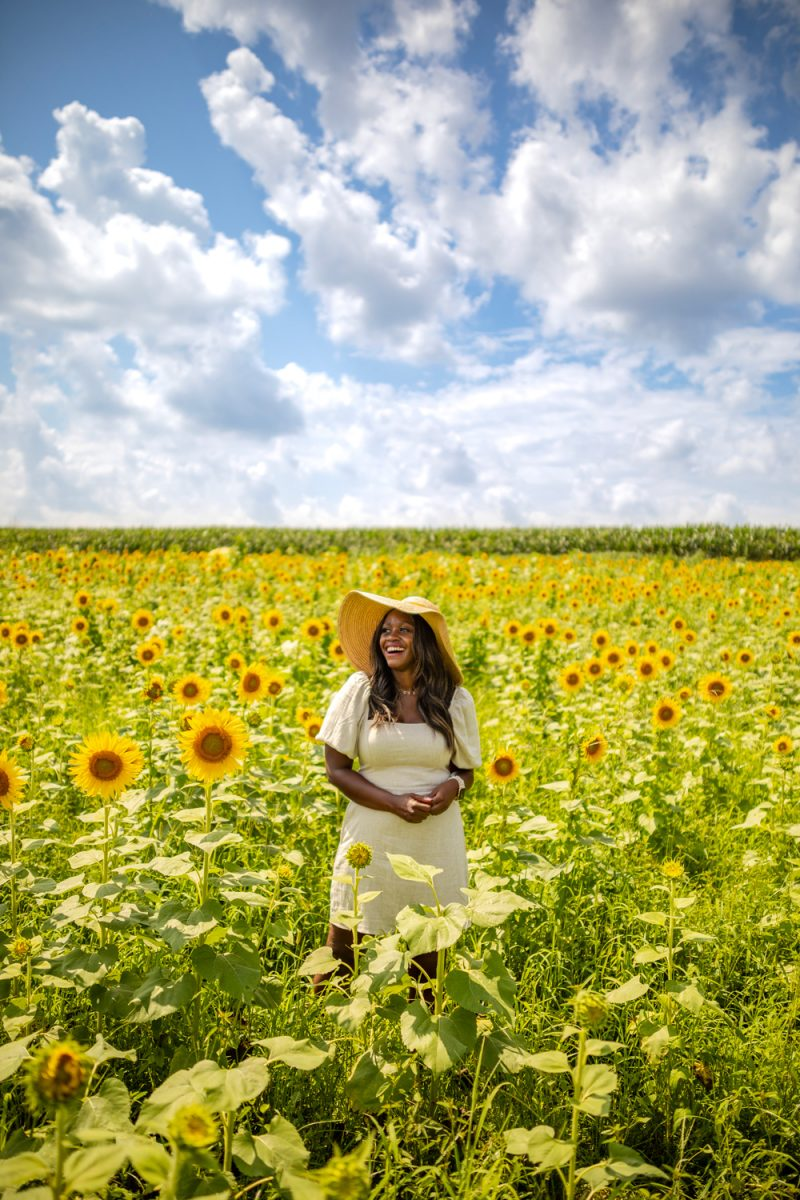 Being 30 by popular D.C. lifestyle blogger, Alicia Tenise: image of Alicia Tenise standing in a sunflower field and wearing a Hat Attack Coco Sunhat and Abercrombie and Fitch Puff-Sleeve Linen-Blend Mini Dress.
