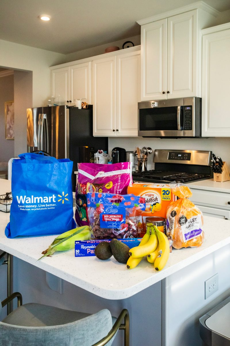 Walmart Express delivery by popular D.C. lifestyle blogger, Alicia Tenise: image of a reusable Walmart shopping bag, ear of corn, avocados, roll of tinfoil, bunch of bananas, bag of assorted chips, Hawaiian sweet bread, a bag of grapes and a box of Goldfish crackers on a kitchen island countertop.
