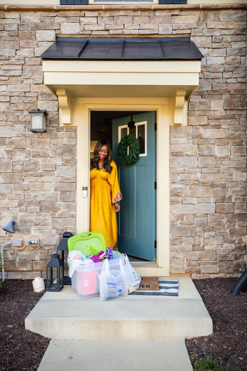 Walmart Express delivery by popular D.C. lifestyle blogger, Alicia Tenise: image of Alicia Tenise wearing a Walmart Scoop Women's V-Neck Cinched Waist Dress and Walmart Scoop Women's Sofia Strappy Flat Sandals while standing in her open front doorway and looking at plastic storage bins containing various goods from Walmart.