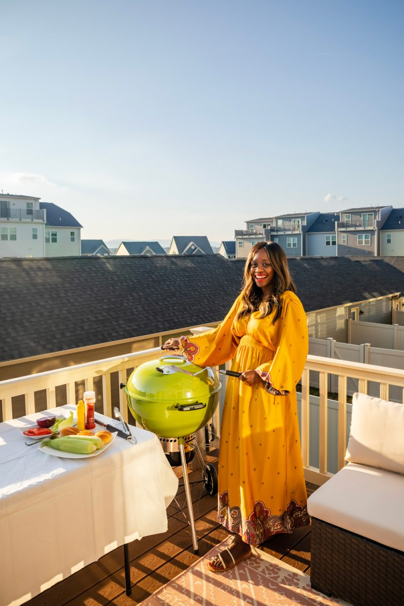 Walmart Express delivery by popular D.C. lifestyle blogger, Alicia Tenise: image of Alicia Tenise wearing a Walmart Scoop Women's V-Neck Cinched Waist Dress and Walmart Scoop Women's Sofia Strappy Flat Sandals while standing on her back deck and grilling food in her lime green Weber grill.